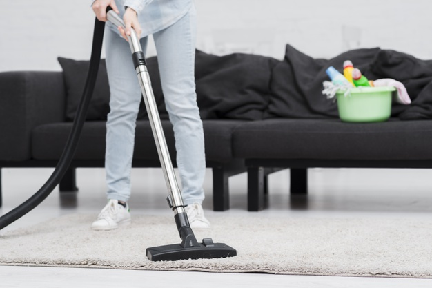 close-up-woman-cleaning-with-vacuum-cleaner_23-2148394900