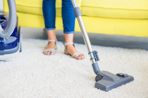 low-section-view-female-janitor-cleaning-carpet-with-vacuum-cleaner_23-2147916518
