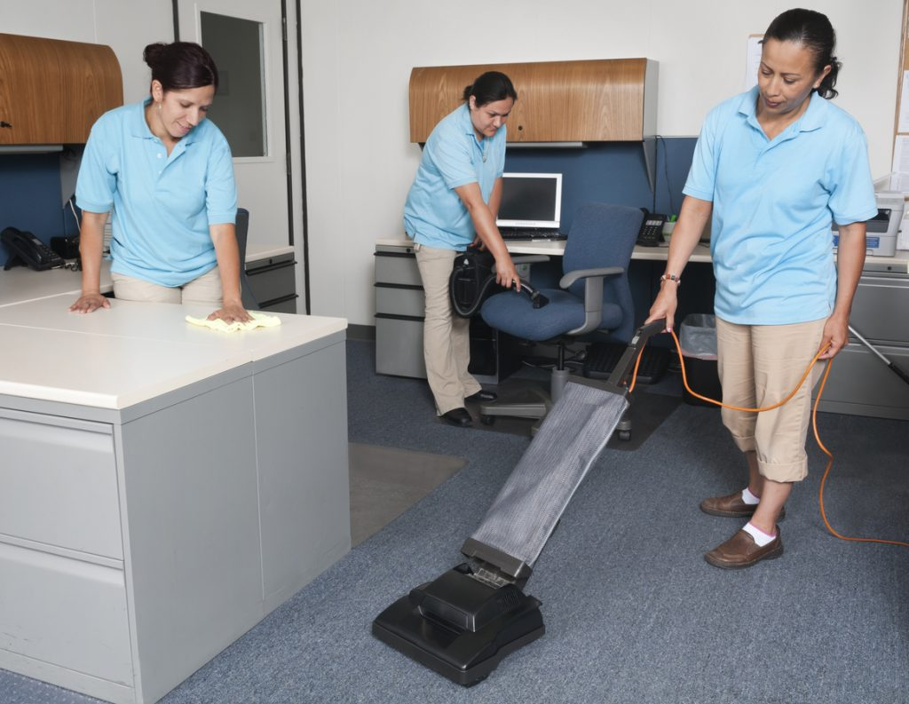 Women from janitorial service cleaning an office